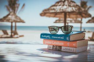 Tisch am Strand mit Büchern, Sonnenbrille und Sonnenschirm